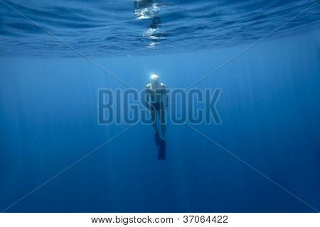 Underwater shoot of a young athlete finning from a depth to surface on a breath hold