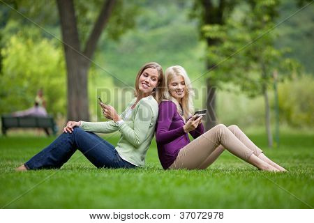 Side view of happy young female friends with cellphones sitting back to back in park