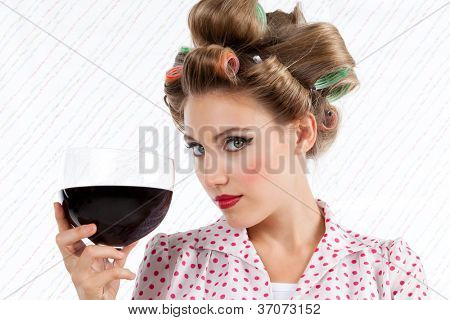 Attractive retro woman holding red wine glass looking at camera