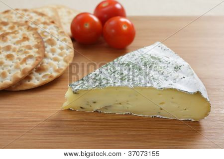 A cheeseboard with a herbed French brie, crackers and tomatoes.