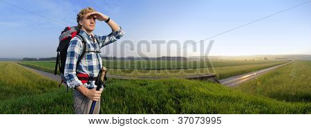 Hiker in vast wheat fields at sunset with a small rural road passing underneath him