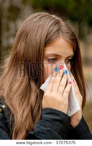 Teenage girl with allergy or cold blowing nose in the handkerchief