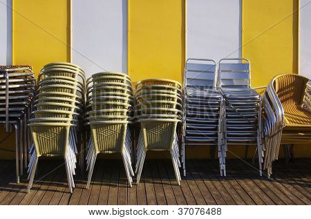 Groups of tables and chairs stacked and chained together against a yellow striped wall