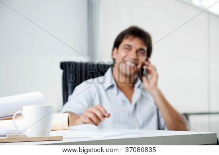Focus on coffee cup with male architect answering phone call in background