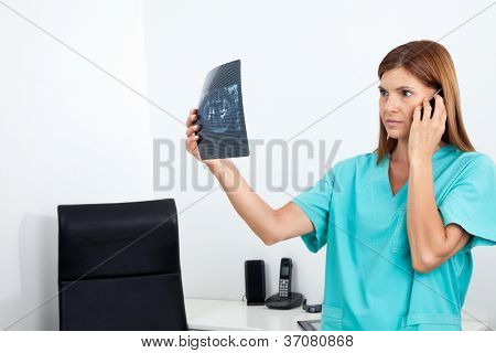 Serious female dentist looking at X-ray report while using cellphone in clinic