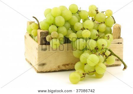 fresh white seedless grapes on the vine in a wooden crate on a white background