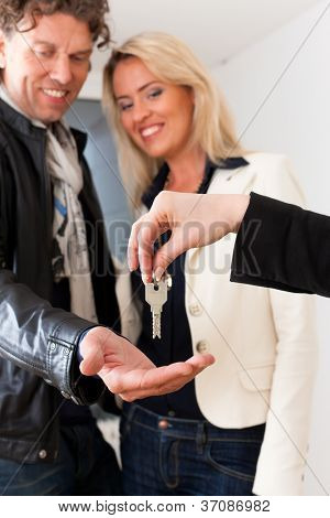 Young realtor is giving the keys to an apartment to a young couple, maybe the purchaser or the tenants