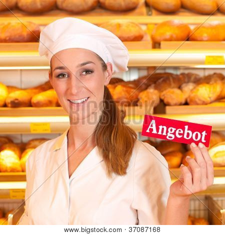 Female baker or saleswoman in her bakery selling fresh bread, pastries and bakery products, she hold a sign in her hand saying