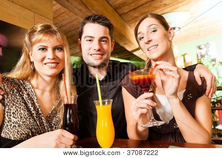 Young happy people drinking cocktails in bar or restaurant; presumably it is a little party