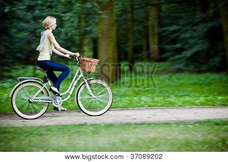 Female biker in a park, intentional motion blur (panning)