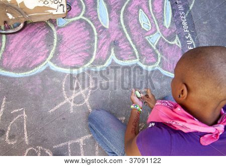 NEW YORK - SEPT 17: A protester writes with chalk on the sidewalk in front of Trinity Church on the 1yr anniversary of the Occupy Wall St protests on September 17, 2012 in New York City, NY.