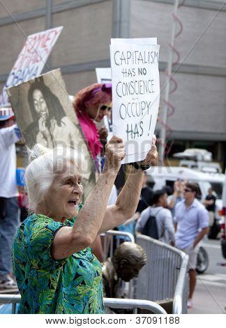 NEW YORK - SEPT 17: A protester holds a sign that reads 'Capitalism Has No Conscience - Occupy Has' on the 1yr anniversary of the Occupy Wall St protests on September 17, 2012 in New York City, NY.