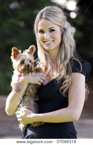 Attractive young woman holding her yorkie