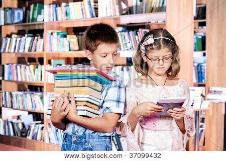 Boy with books pile and girl with e-reader