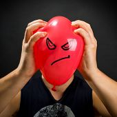 picture of angry smiley  - Man squeezing red balloon with angry smiley - JPG