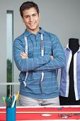 stock photo of cross-dresser  - Portrait of young male tailor standing arms crossed by table with mannequin in background - JPG
