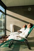 Young couple relaxing in wellness spa on liege, they enjoy the sun