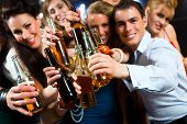 stock photo of flirt  - Young people in club or bar drinking beer out of a beer bottle and have fun - JPG