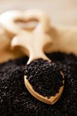 image of bengali  - black cumin or caravay or onion seeds in heart shape wooden spoon - JPG