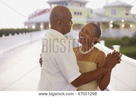 Senior couple dancing on pier