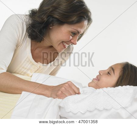 Mother tucking her daughter into bed