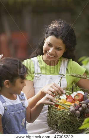 Woman and girl with basket of vegetables