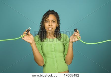 Clueless young woman holding two ends of an extension cord