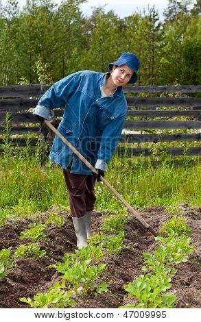 Girl Spud Potatoes In The Garden