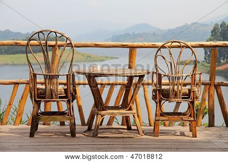 Wicker Deck Chairs With Coffee On A Table And A Lake View