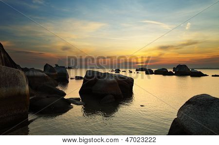 Dramatic sunrise in rocky beach