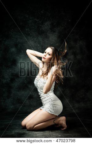 beautiful young woman in short white dress studio dark background
