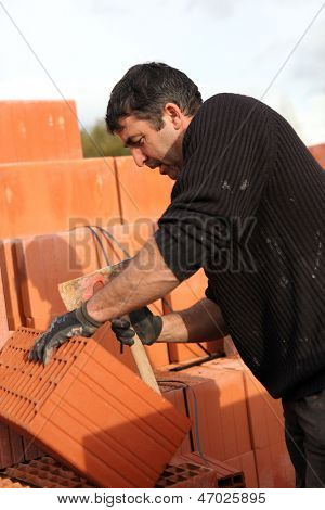 Mason making adjustments to brick