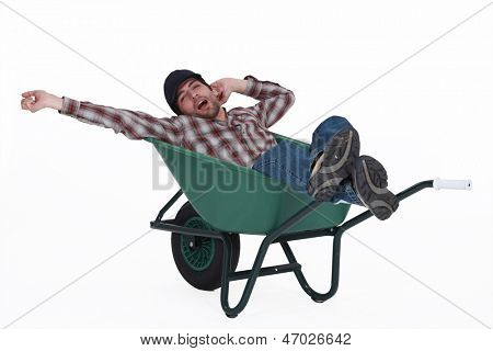 Man dozing in a wheelbarrow