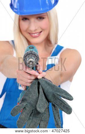Tradeswoman aiming a screwdriver