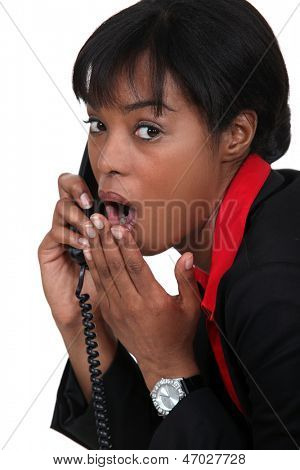 black businesswoman on the phone  shocked at sensational news