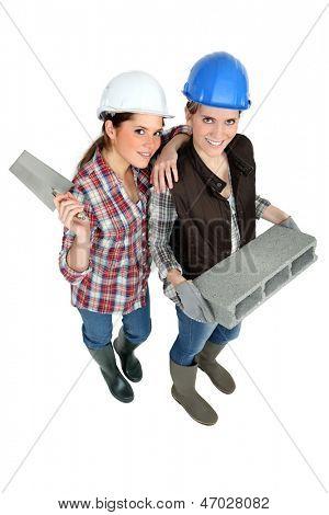 two female builders posing