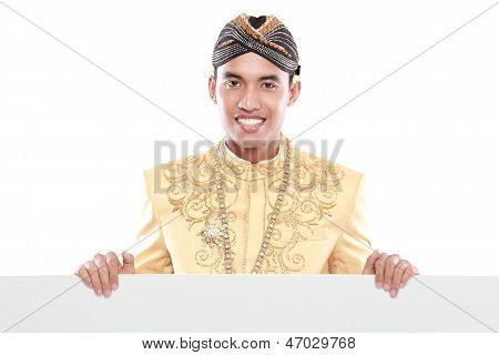 Man Wearing Traditional Dress Of Java Holding Blank Board
