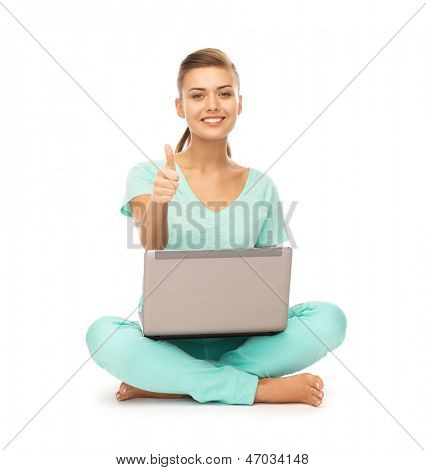young girl sitting on the floor with laptop showing thumbs up