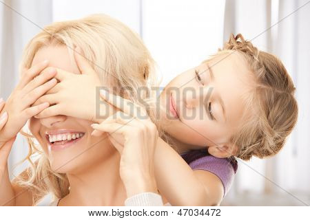 picture of mother and daughter making a joke or playing hide and seek