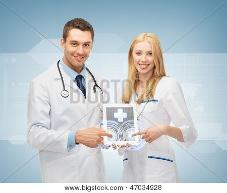 two young doctors pointing at tablet pc with medical app
