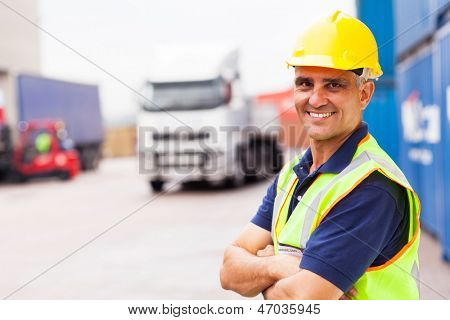 cheerful senior shipping company worker standing outside warehouse with arms crossed