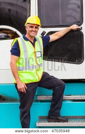 senior harbor forklift driver standing on forklift in container depot