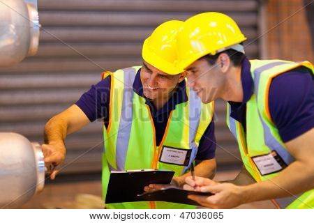 warehouse co-workers in safety gear inspecting machinery