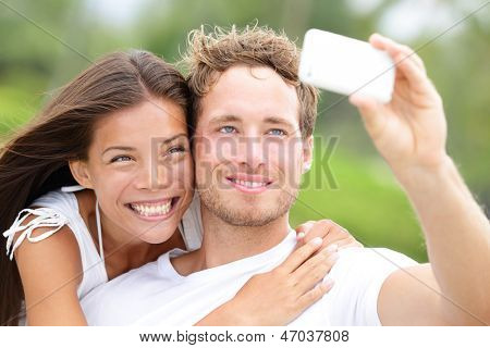 Couple fun taking self-portrait picture photos with mobile smart phone or pocket camera outdoors. Happy multiracial young couple in love taking pictures together on summer vacation. Man and woman