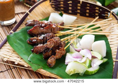 Satay or sate, skewered and grilled meat, served with peanut sauce, cucumber and ketupat, Malaysia or Indonesia food. Traditional Malay food. Hot and spicy Malaysian dish, Asian cuisine.