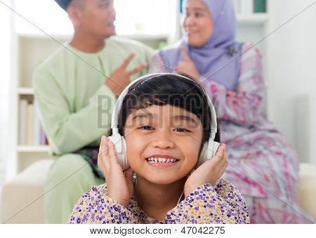 Muslim girl listening to song at home. Southeast Asian family living lifestyle. Happy smiling Malay parents and child.