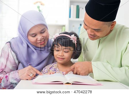 Pais muçulmanos malaios ensinar a criança a ler um livro. Sudeste asiática família em casa.