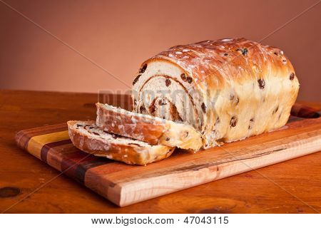 Homemade rolled cinnamon raisin bread on a wooden cutting board.
