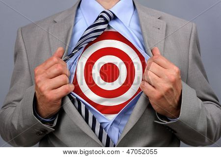 Businessman in classic superman pose tearing his shirt open to reveal target symbol on chest concept for human resources and recruitment