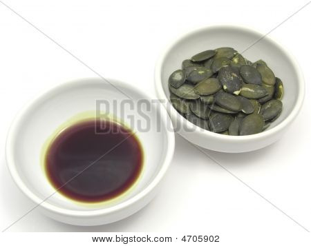 Two Bowls Of Chinaware With Pumpkin Seeds And Pumpkin Seed Oil